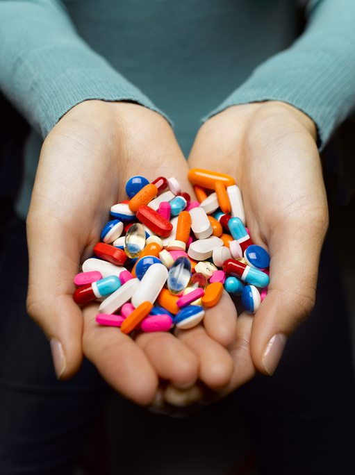 Woman holding pile of pills in cupped hands, close-up